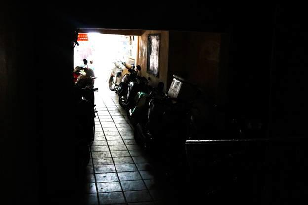 """Tầng trệt để xe khu B6 Thành Công vừa tối vừa chật, chỉ để được số lượng nhỏ. """"Ngày nắng họ để xe bên ngoài còn có lối mà lên chứ ngày mưa xe xếp chật cả lối đi lên cầu thang."""" - Chị Hồng (người bán hoa quả chợ Thành Công) chia sẻ."""