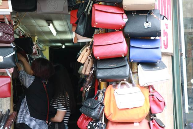 Cửa ngõ 15 Hàng Đào cũng được tận dụng triệt để trong việc bày bán túi xách. Mặc dù không gian khá chật hẹp nhưng nhiều người đến mua hàng.
