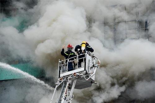 Lực lượng cứu hỏa tại hiện trường vụ cháy quán karaoke ở Cầu Giấy làm 13 người thiệt mạng.