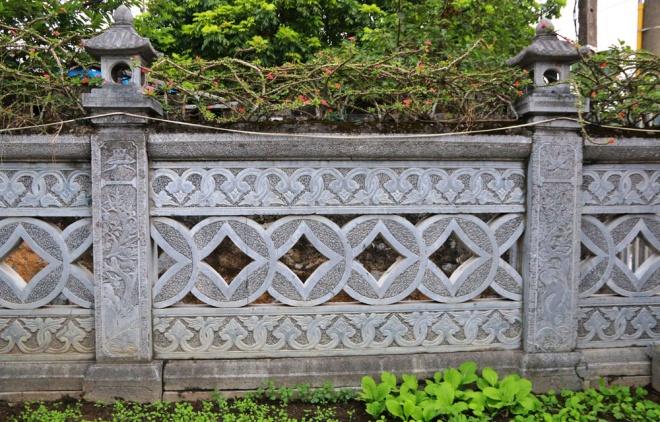 Bức tường bao quanh bằng đá, trang trí hình đồng tiền âm dương cầu kỳ. Nhà nằm trên diện tích đất đắc địa trong làng.
